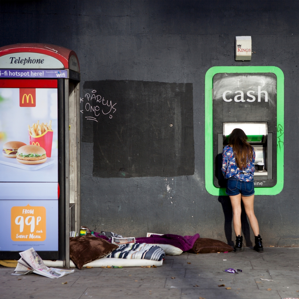 A young woman stands at a cash point, on a black city wall which has paint patches and graffiti reading 'Party One'. There is a phone box with a Macdonald's advert and on the floor are the possessions of a homeless person.