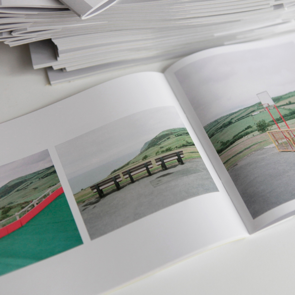 The zine is open to two pages showing landscape photographs of an empty leisure facility